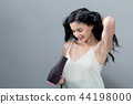 Beautiful young woman holding a hairdryer 44198000