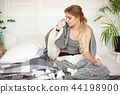 Miserable young woman sitting on the bed wrapped in warm blanket feeling sick with flu 44198900
