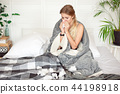 Miserable young woman sitting on the bed wrapped in warm blanket feeling sick with flu 44198918