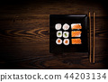 Various kinds of sushi served on wooden table. 44203134