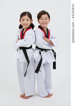 Children education. Taekwondo, little boy and girl practice martial arts in white background 239 44203641