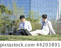 Cheerful young businessman walking in park near office building in the background. Spend time in park with collegue near office. 253 44203891