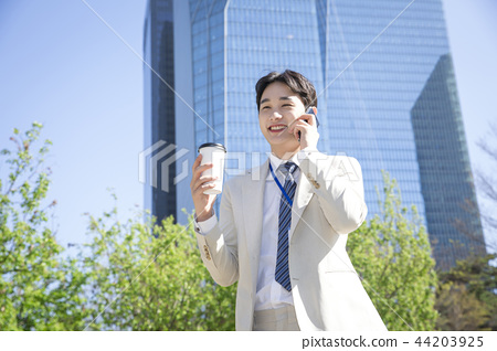 Cheerful young businessman walking in park near office building in the background. Spend time in park with collegue near office. 212 44203925