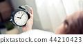 Banner website woman turn off alarm clock 44210423