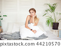 Caucasian sleepy young attractive woman feeling drowsy after woke up, sits on the bed having bad 44210570