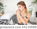 Caucasian young attractive woman waking up with good mood, happy woman sits on the bed in the 44210688