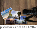 Camera and stack of photos on wooden background 44212962