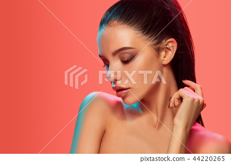 High Fashion model woman in colorful bright lights posing in studio 44220265