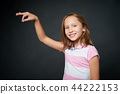 Smiling girl holding imaginary thread in her fingers 44222153