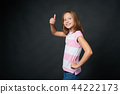Happy school age girl gesturing thumb up 44222173