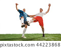Football players tackling for the ball over white background 44223868