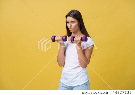 Feeling exhausted. Frustrated young woman in white shirt exercising with dumbbells and serious look 44227133