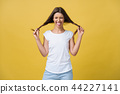 Studio shot of charming caucasian girl isolated on yellow background. Indoor portrait of pretty lady 44227141