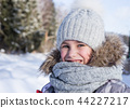 Winter portrait of happy little girl wearing knitted hat and scarf. 44227217