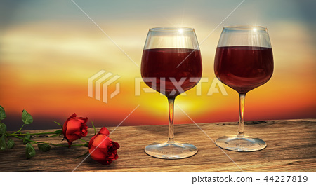 Two wine glasses filled with wine during sunset 44227819