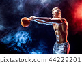 Concentrated muscular man doing exercise with kettlebell 44229201