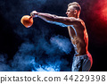 Concentrated muscular man doing exercise with kettlebell 44229398