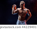 Concentrated muscular man doing exercise with kettlebell 44229401