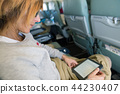 Woman reading ebook sitting inside airplane 44230407