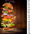 Big tasty burger with flying ingredients. 44231979