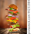 Big tasty burger with flying ingredients. 44231984