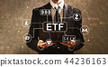 Cryptocurrency ETF theme with businessman holding a tablet compu 44236163