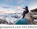 Mountaineer sitting on rock at the peak mountain 44236620