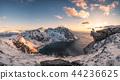 Panorama of Mountaineer sitting on rock on peak 44236625