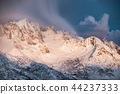 Golden sunrise on snow mountain with clouds 44237333