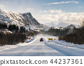 Car driving on snowy road with mountain range 44237361