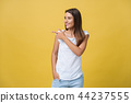 Profile of a woman pointing on copy space for an advertisement isolated on a yellow background 44237555