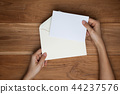 A female hand hold an envelope and post card  44237576