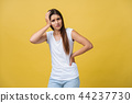 Young woman is suffering from a headache against a yellow background. Studio shot 44237730