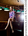Smiling woman sitting on billiards table with cue. 44253008