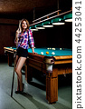 Beautiful woman stands near billiards table with cue. 44253041