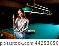 Smiling woman sitting on billiards table with cue. 44253050