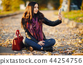 brunette girl using phone while at the park 44254756