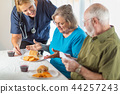 Nurse Serving Senior Couple Lunch at Nursing Home 44257243