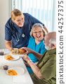 Nurse Serving Senior Couple Lunch at Nursing Home 44257375