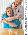 Doctor Helping Senior Woman With Shoulder Therapy 44257384