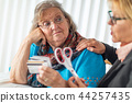 Financial Consultant Hands Scissors to Senior Lady 44257435