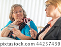 Financial Consultant Hands Scissors to Senior Lady 44257439