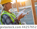 Female Construction Worker Using Drone at Job Site 44257652