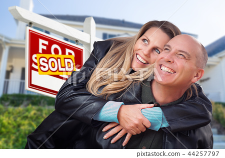 Happy Couple Hugging in Front of Real Estate Sign  44257797