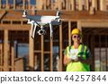 Female Flies Drone Inspecting Construction Site 44257844