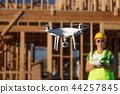 Female Flies Drone Inspecting Construction Site 44257845