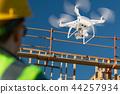 Female Drone Pilot Inspects Construction Job Site 44257934