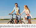 happy young couple riding bicycles at seaside 44261153