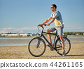 happy man riding bicycle along summer beach 44261165