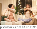 happy female friends having pillow fight at home 44261195